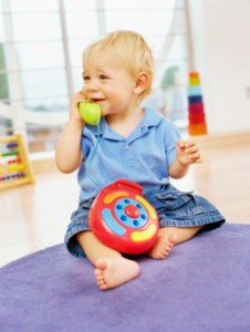 baby boy playing with a toy telephone