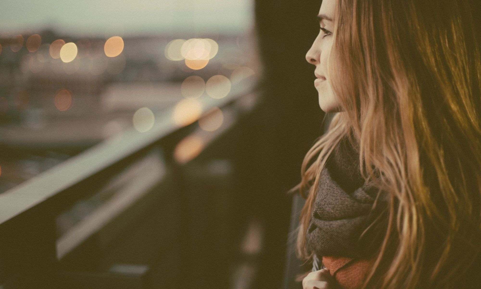 Woman looking out over city at dusk