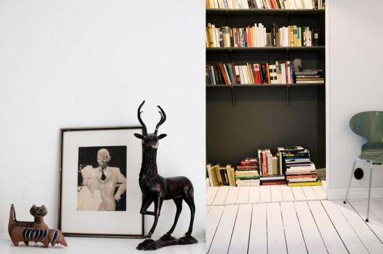 Semi-hidden bookshelf with black wall and shelfs.