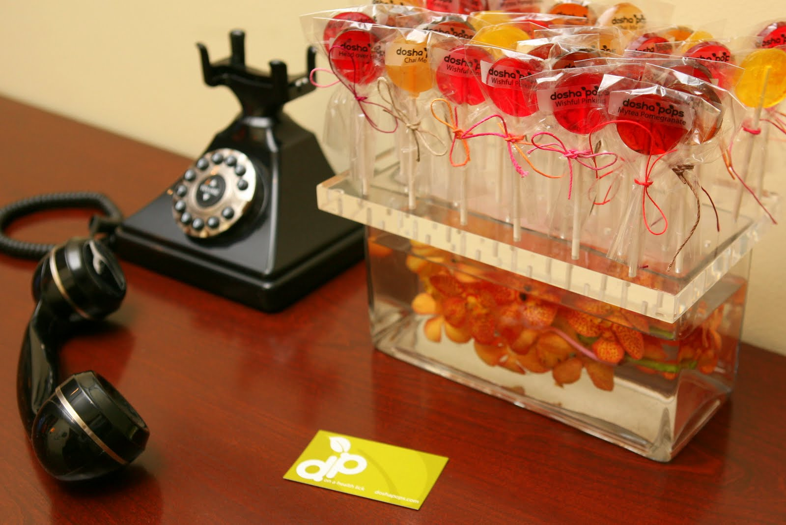 Dosha Pops display stand holding lollipops and flowers on a table with business card and old fashioned phone