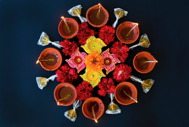 Lit clay oil lamps, flowers and Dosha Pops arranged on a black background