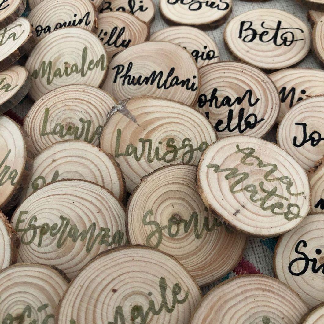 rodajas de madera con el nombre de los invitados en lettering