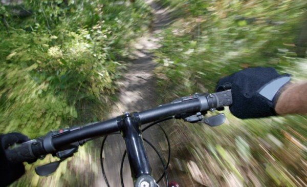 Man mountain biking on trail, view over handlebars (blurred motion)
