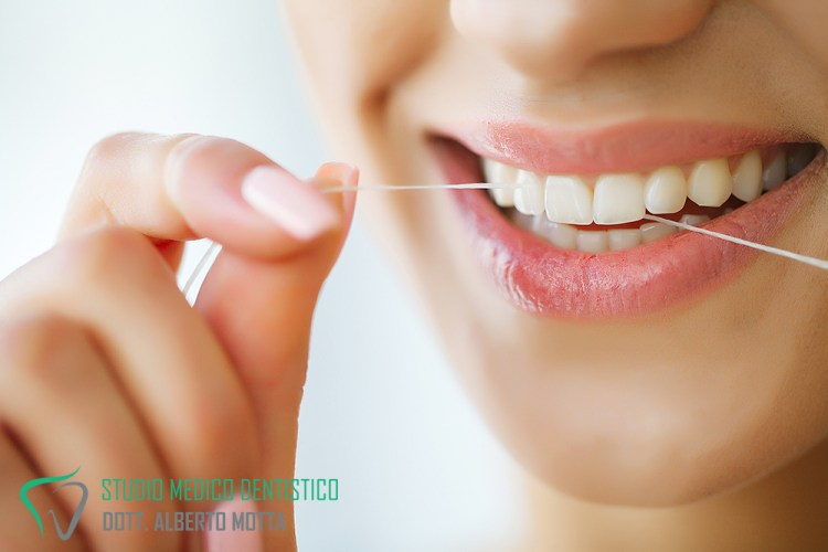 Pulizia dei denti con filo interdentale