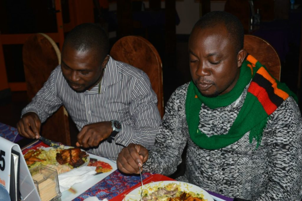 Kolo and Dotun Roy digging into fried rice and chicken