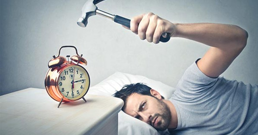 hitting alarm clock with hammer