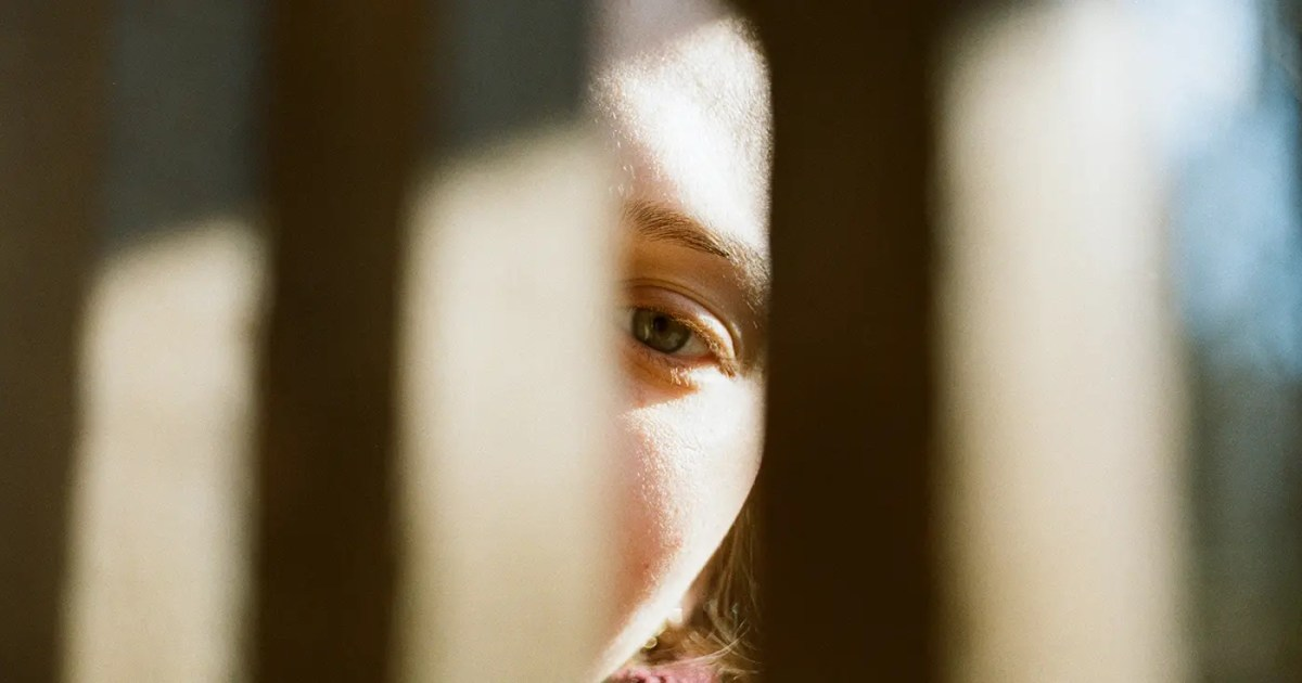 Doubleblind: a woman looking through what seems to be stairs.