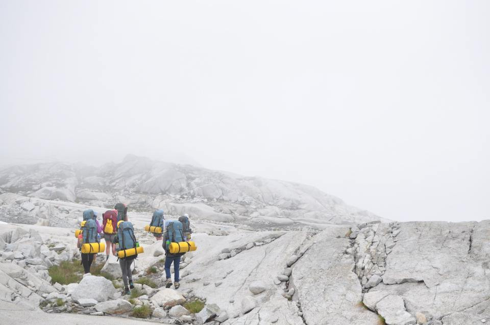 A group of hikers climbing a misty-covered mountain the the fog