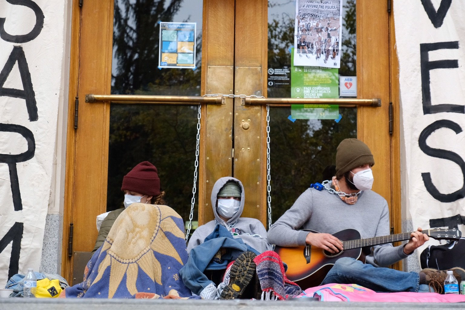 three people sit in front of wood doors framed by banners that read disarm and divest