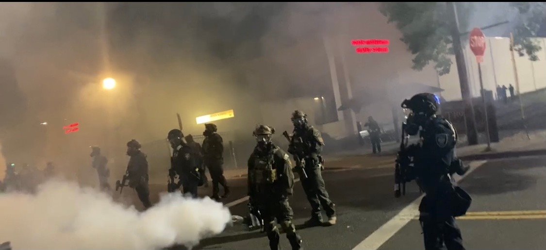 Nighttime photograph taken of a dozen riot cops standing behind a smoke canister in the middle of a portland street.