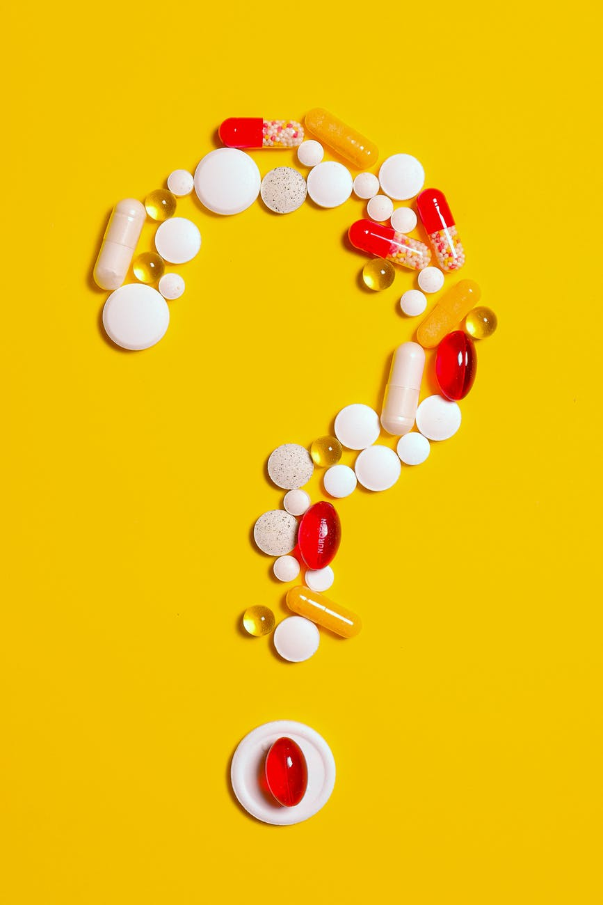A bunch of medications and assorted pills made into the shape of a question mark on a yellow background