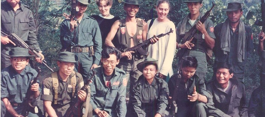 A group photo of student militants posing with rifles and other guns, while two white women stand behind them and smile.