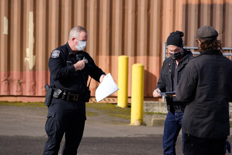 Three men stand in a group. On the left hand side is a uniformed police officer wearing a mask over most of his face and a gun on his hip, holding some papers in his left hand. On the right-hand side are two men in black denim jackets and beanies, reading something from the papers