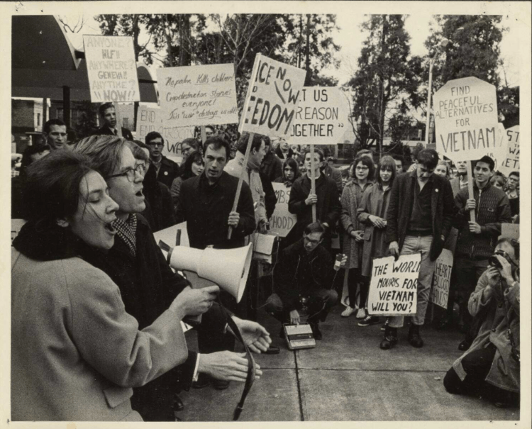 "Black and white photograph of university of oregon students gathering for an anti-war demonstration in 1966. In the foreground, a man and a woman appear to be shouting or singing into a megaphone, while the background has dozens of people lined up holding signs with slogans like ""find peaceful alternatives for Vietnam"""