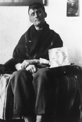 Black and white photograph of Willem Arondeus sometime around 1921. He is seated his hands crossed on his lap and what appears to be a book on the table next to his chair.