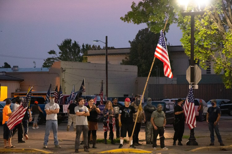 A line of far-right protesters wielding American flags and Blue lives matter flags are set up in a parking lot across from a Black Unity protest in downtown Springfield. Everyone is slouching and masked, except for a few men and women at the front of the group.