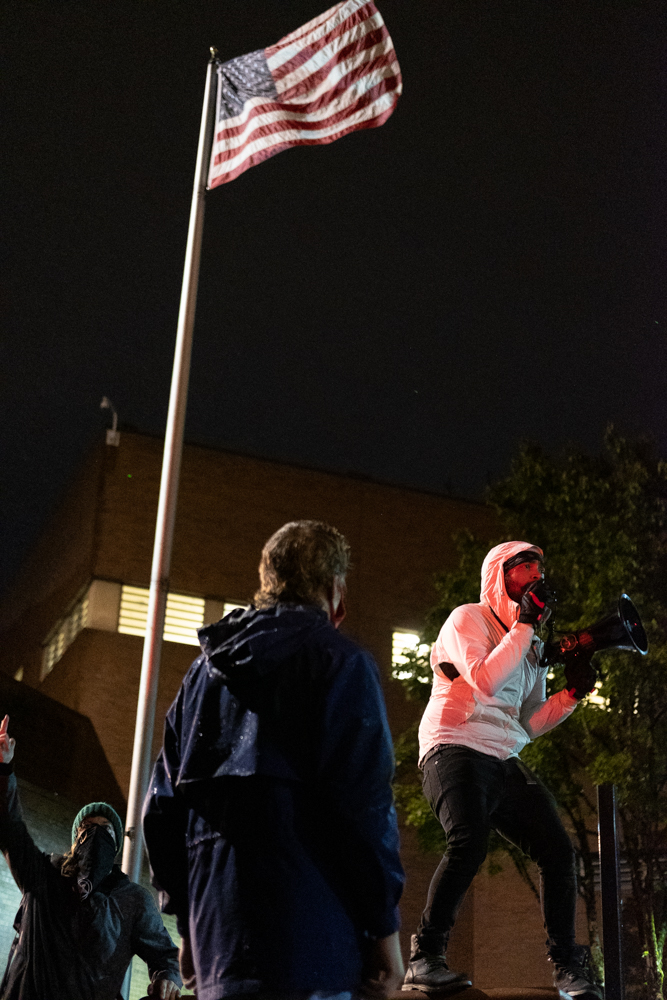 Photo of a black man in a white jacket and black mask speaking into a megaphone beneath an american flag at the lane county jail. an older white person is in the foreground looking up at him.