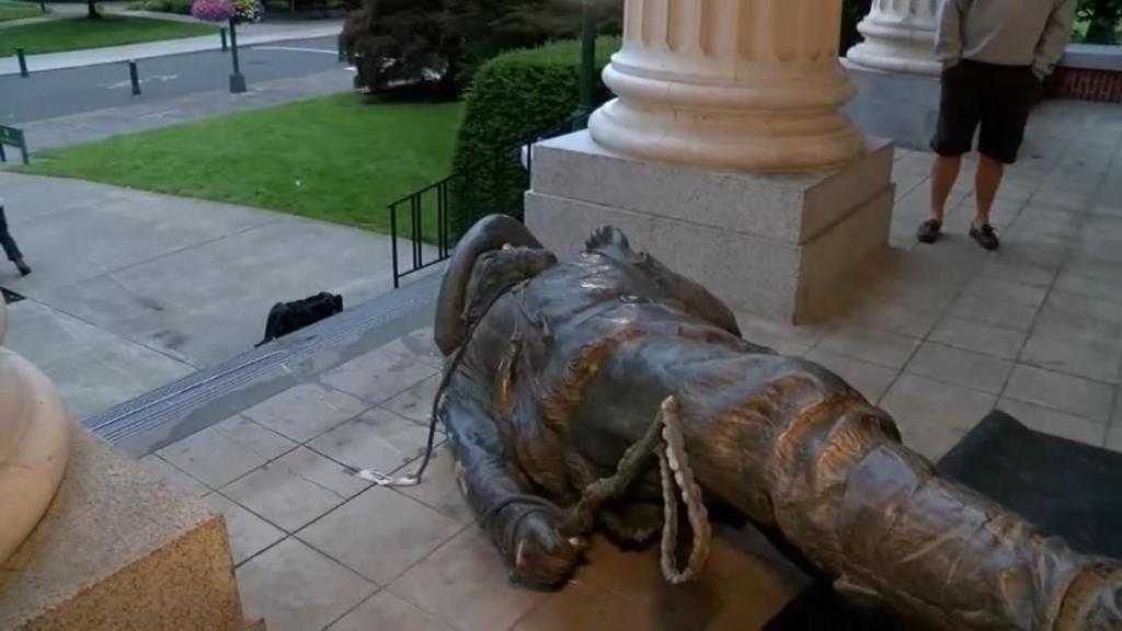 Photograph of the the Pioneer statute laying face-down on the steps of Johnson Hall at the University of Oregon campus