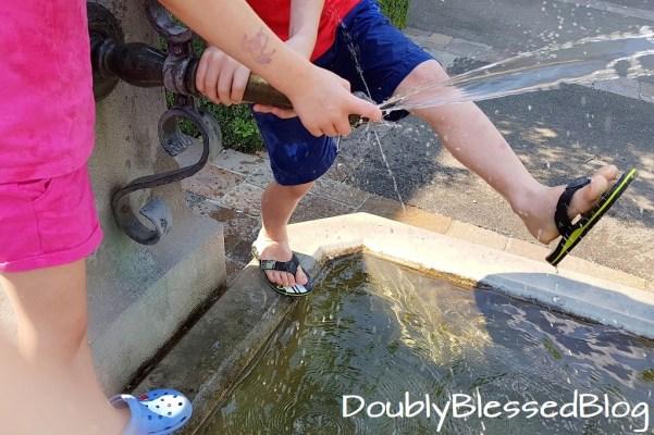 Abkühlung für die Kinder in der Sommerhitze - Den Dorfbrunnen unsicher machen