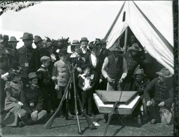 Group gathered around a man playing the dulcimer at Camp Black, Long Island, New York