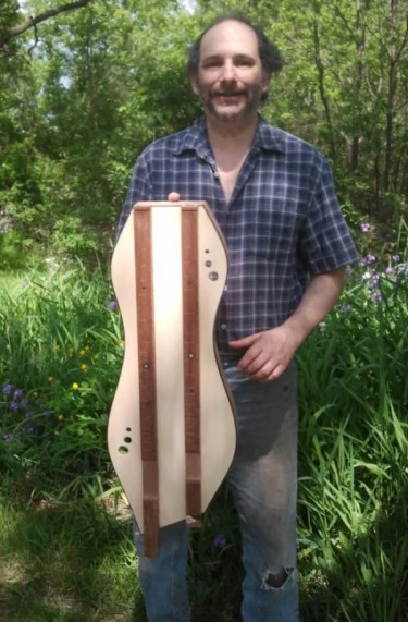 Portrait of a well-dressed dulcimer maker standing in the garden.