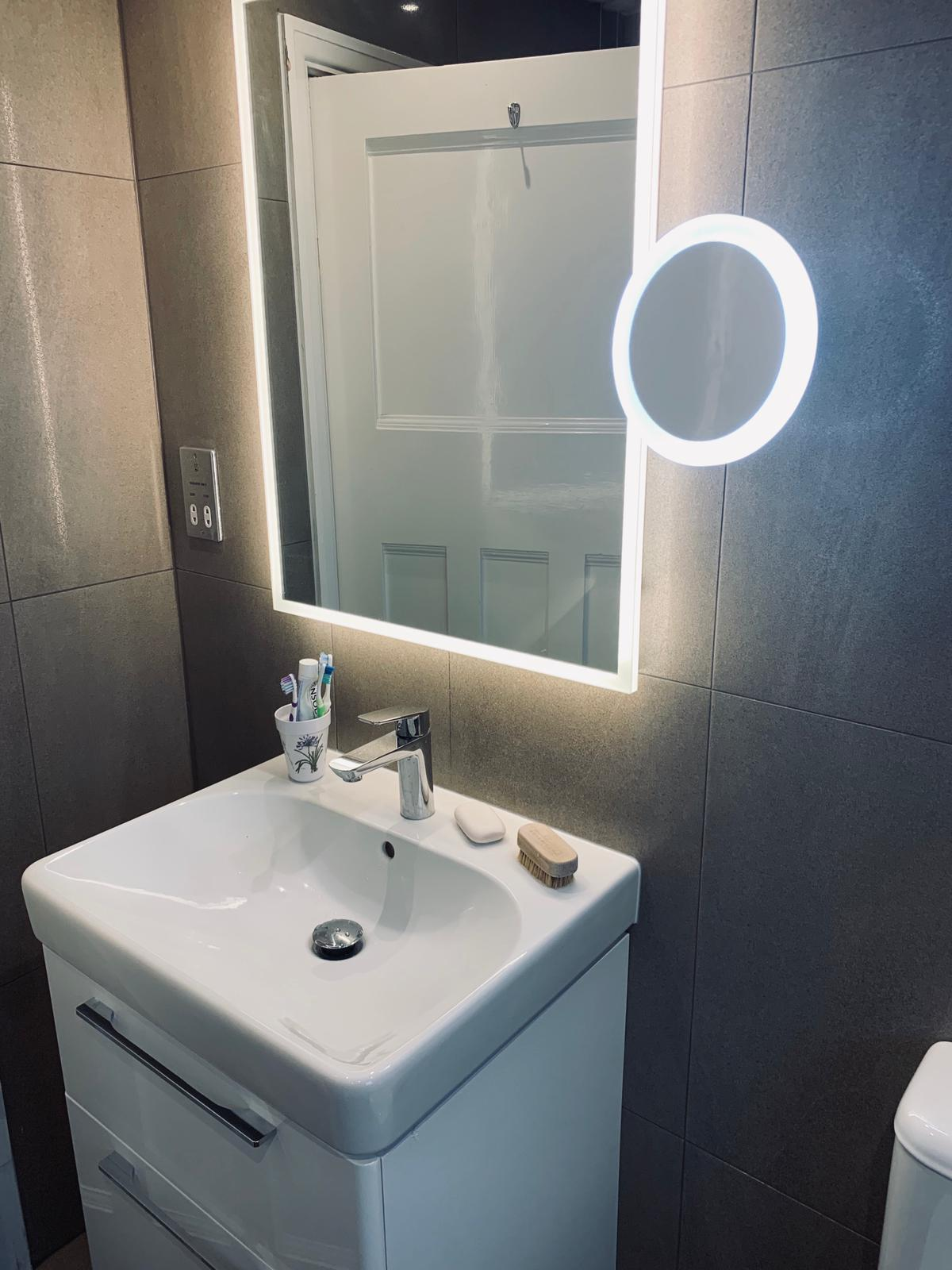 White bathroom storage with illuminated mirror