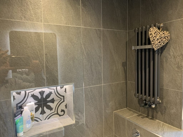 Shower recess with mood lighting and feature tile along side a small charleston bar in an anthracite finish