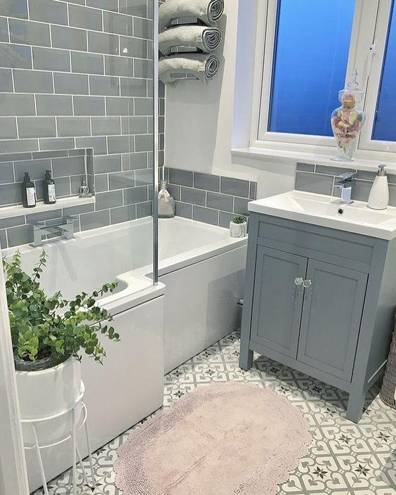 family bathroom with l shaped shower bath and floor standing basin unit