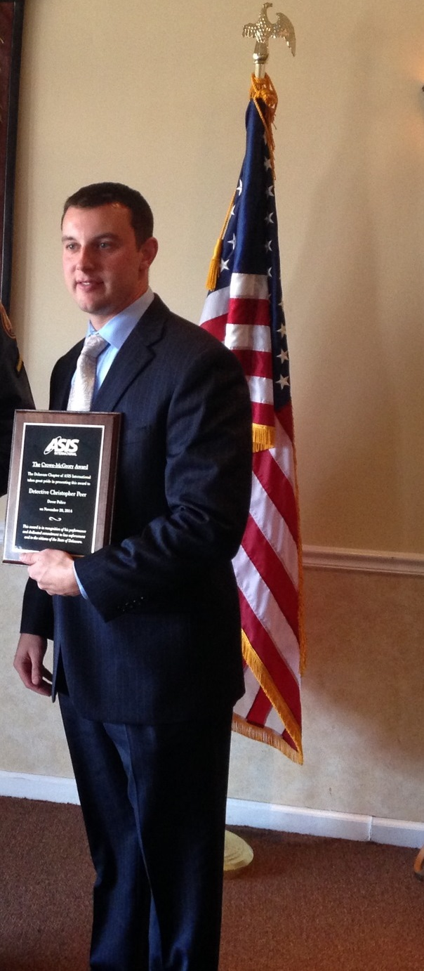 Detective Peer stands with his award after being recognized at the ASIS Law Enforcement Luncheon
