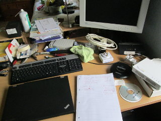Desk surface with laptop, keyboard, display and notepad.