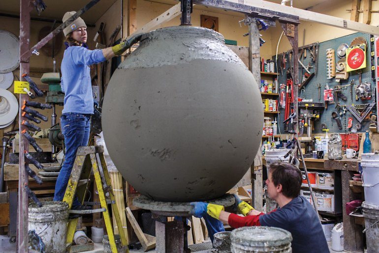 People working on large clay urn