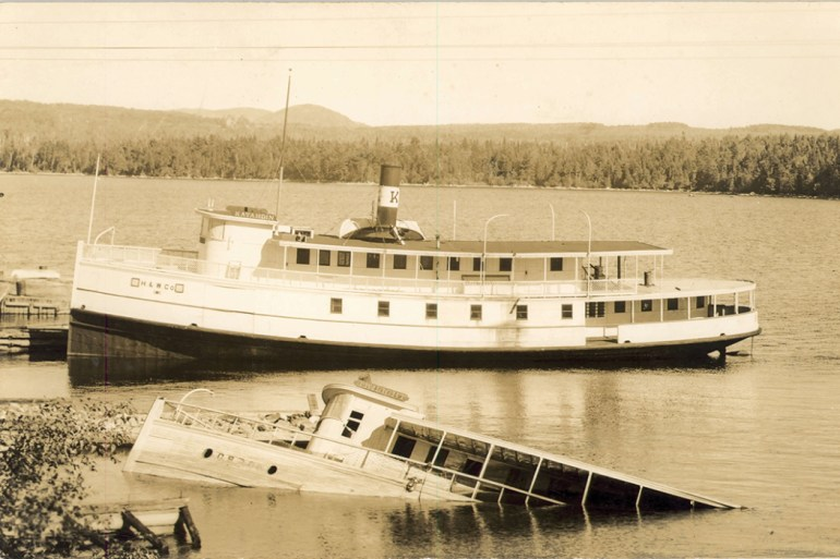 old photo of a steamboat next to another sinking steamboat on Moosehead Lake