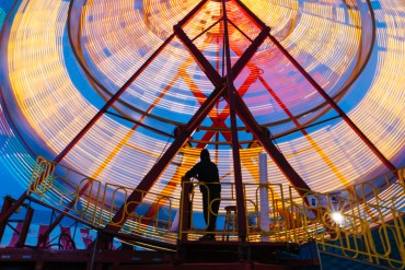 A carnival worker mans the Ferris wheel on the opening night of the Fryeburg Fair.
