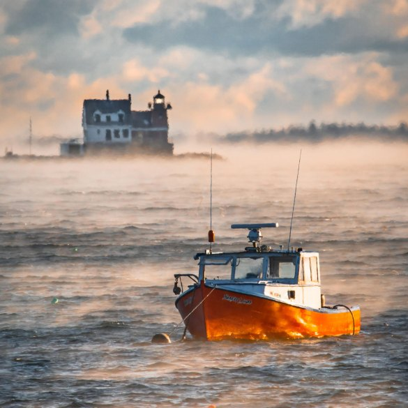 A red lobster boat sits in her mooring with Rockland Breakwater Light in the background, both surrounded by sea smoke in the frigid air this morning.