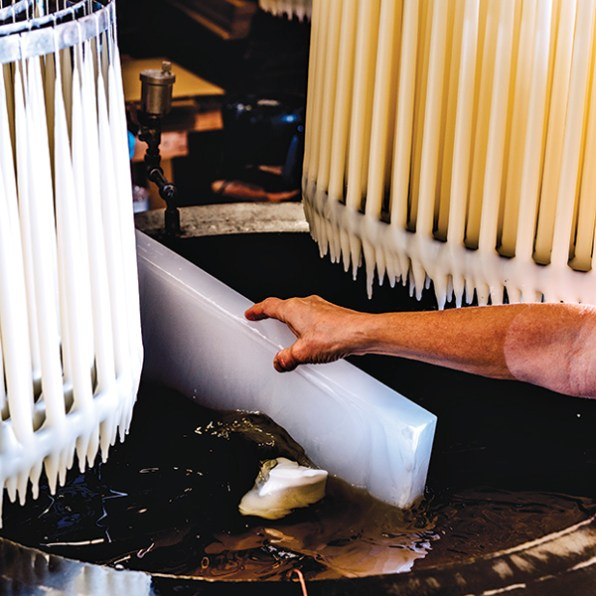 Danica Design employee adding wax to dipping machine