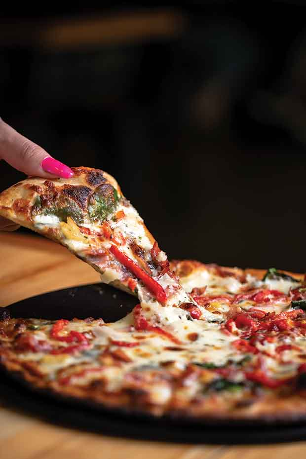 wood-fired pie topped with peppers, spinach, and prosciutto