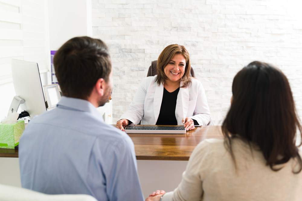 Female doctor smiling at her desk at couple