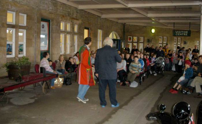 Colin regaling the audience, despite the occasional speeding train passing through the station