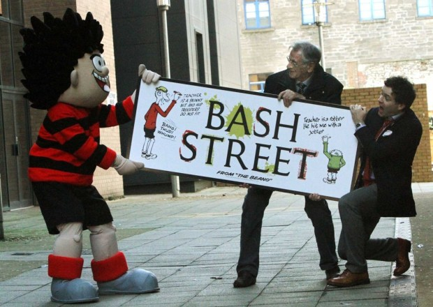 Pictured in the newly named 'Bash Street' in Dundee on Wednesday 26th February 2014, is Dennis The Menace trying to steal a copy of the sign, with Beano Editor Mike Stirling, right, and Dave Sutherland, who draws Dennis. Photo: The Courier. Reproduced with permission