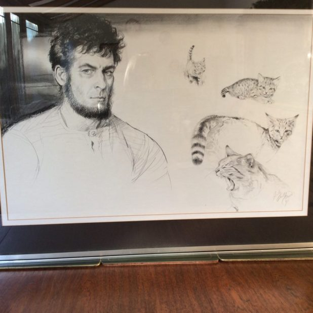 "An illustration of author Mike Tomkies, ""The Wilderness Man"", and his wild cat Kitten, painted by Shirley in 1981. As well as being a writer Mike, who lived on Loch Shiel and he and Shirley were great friends. She illustrated some, if not all, of his books describing his life in the wilds of Scotland. He died in October 2016."