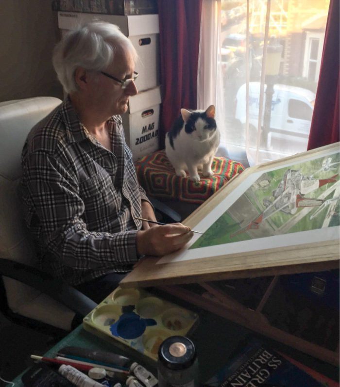 """Graham Bleathman with his cat """"helper"""", 13-plus Pixel, who usually sits on his box in the afternoon supervising and doing his Neighbourhood Watch duty. Photo: Katie Bleathman"""
