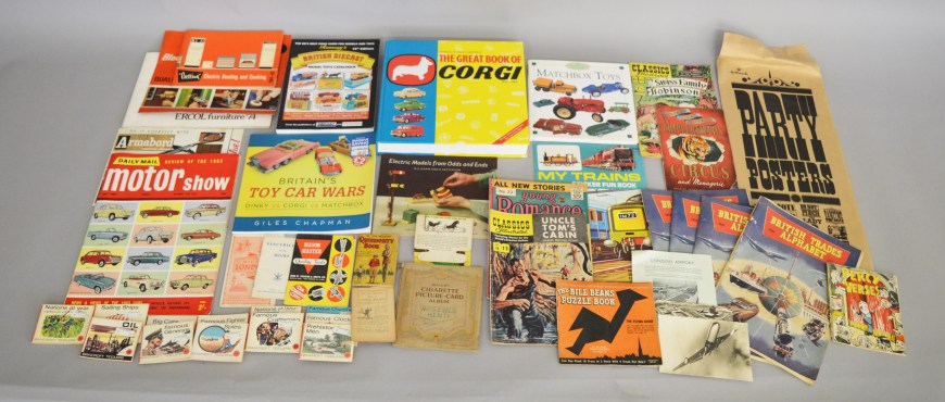 A small quantity of toy related books including 'The Great Book of Corgi' and 'Ramsay's Diecast Catalogue 14th Edition' together with a varied selection of books, publications and other paper ephemera including a vintage Chipperfield's Circus Programme, a Will's Cigarette Card Album containing a quantity of 'Household Hints' cards, humorous 'Hallmark' posters, 1974 Ercol Furniture Catalogue, two Aircraft Postcards etc.