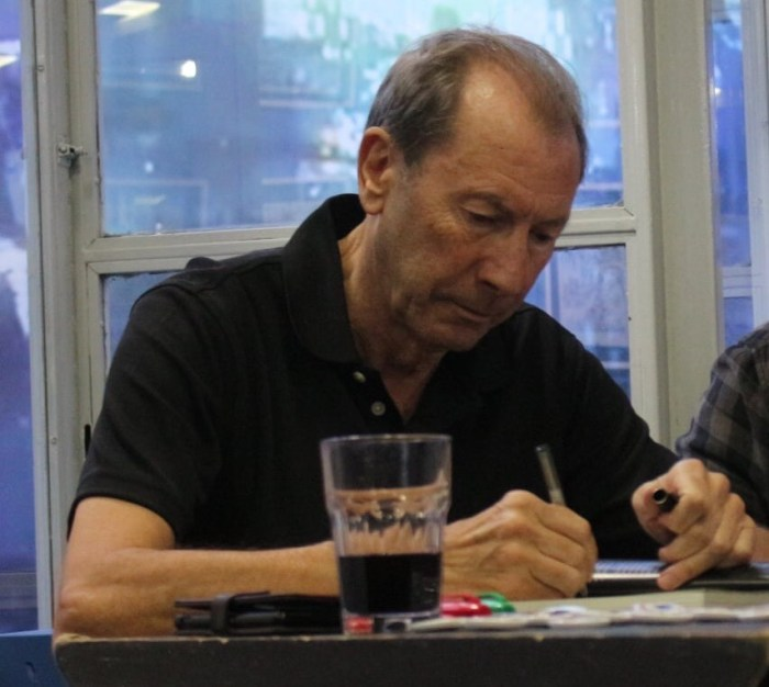 See this guy? Look. See the concentration... the focus... the dedication to service etched into every line... That's V for Vendetta artist David Lloyd at a recent signing, not only enjoying the privilege of meeting nice people but also selling volumes of Aces Weekly via the coded access cards the team produce that all come with a free