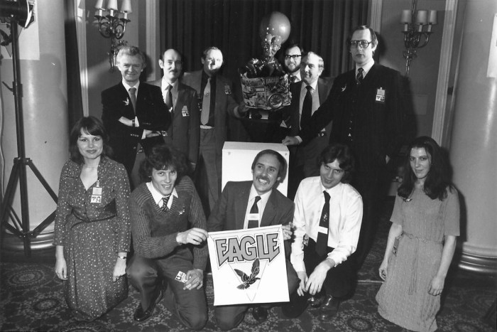 Fleetway staff at the launch of New Eagle in 1982 at the Waldorf Hotel, London, stage managed by Barrie Tomlinson.  Top Row, left to right: Jack Cunningham (art staff), John Jackson (art staff), Doug Church (art editor), the Mekon, Roy Preston (writer), Sid Bicknell (Fleetway editor), then Barrie Tomlinson, standing. Bottom Row, left to right: Barrie's secretary, Debbie Watts; Paul Bensberg (art staff);  David Hunt, holding the Eagle logo; Ian Rimmer (assistant editor); and Janet Dixon (sub editor). Photo courtesy Barrie Tomlinson