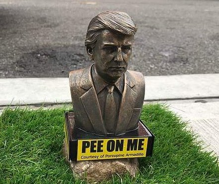 Small statues of Donald Trump appear with signs saying 'pee on me'