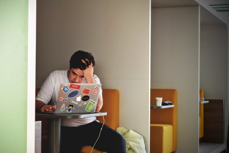 A picture of a young man working on his laptop.