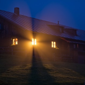 A picture of a bright light shining out of a cabin at night.