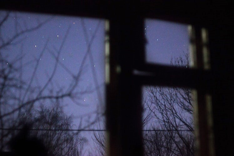Looking out a window dreaming of the night.