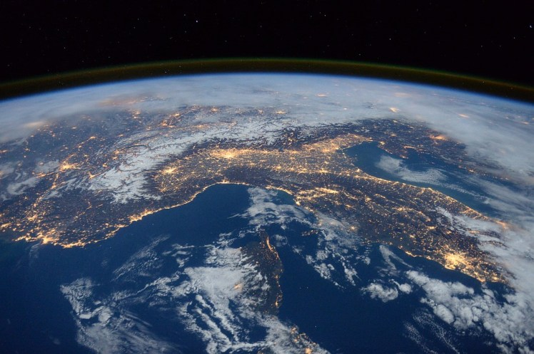 Lights shine up from the Earth as seen from space.