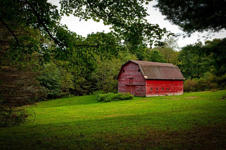 A red barn in an open field.